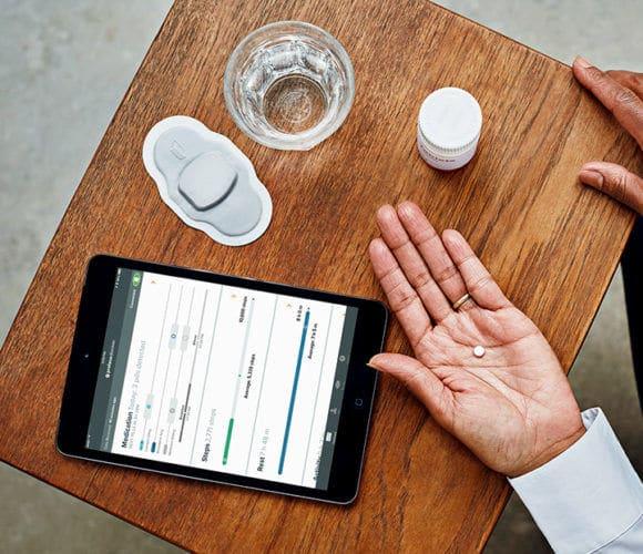 הכדור ביד, מדבקה ואייפד עפ אליקציה על שולחן. וגם כוס מים